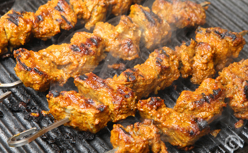 Indian lamb tikka kebabs cooking on hot